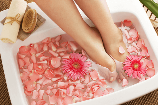 feet in a soaking in tub with flowers
