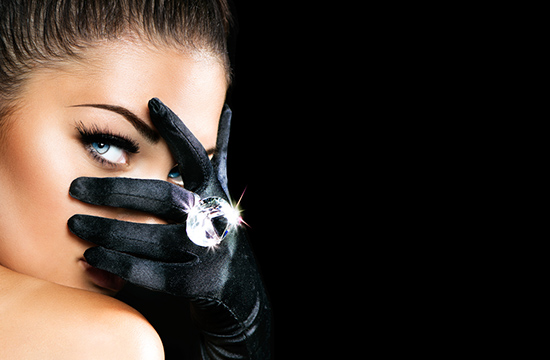woman peeking through black gloved hand