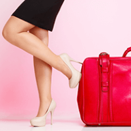 lady in heels with red luggage