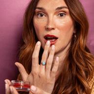 transwoman putting on lipstick
